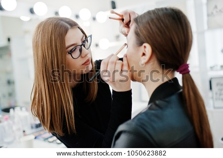 Make up artist work in her beauty visage studio salon. Woman applying by professional make up master. Beauty club concept.