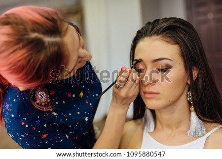 Make-up artist working in studio with young beautiful woman. #1095880547