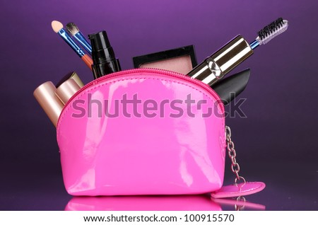 Make up bag with cosmetics and brushes on violet background