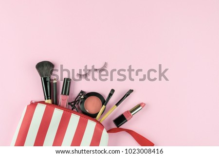 Make up bag with various cosmetics and brushes isolated on pink background, Top view, Beauty concept Foto stock ©