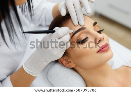 Shutterstock Make-Up. Beautician Hands Doing Eyebrow Tattoo On Woman Face.Permanent Brow Makeup In Beauty Salon. Closeup Of Specialist Doing Eyebrow Tattooing For Female. Cosmetology Treatment. High Resolution