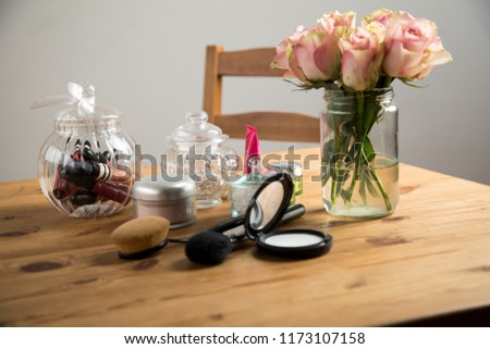 Make-up beauty desk with fixing compact, powder brush, oval brush, lip gloss and a bouquet of pink Cezanne roses