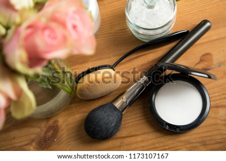 Make-up beauty desk with transparent fixing powder compact, powder brush, oval brush, cotton pads and a bouquet of pink Cezanne roses