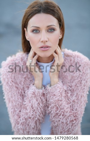 Make up brown straight clean hair woman girl open forehead green eyes neck pink coat jacket white shirt stays poses camera look up hands fingers touch head face chin grey asphalt background street day