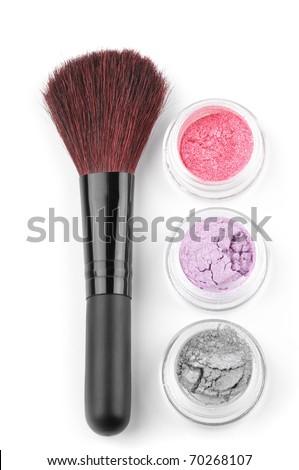 Make-up brush and powder eye shadows in jars isolated on white background.
