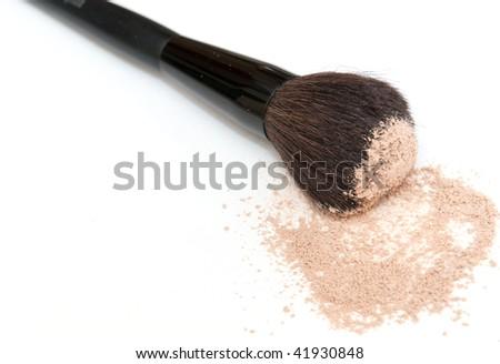 Make up brush near the spilled powder on a white background