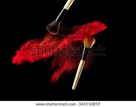 Make-up brush with powder explosion on black background