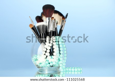 Make-up brushes in a bowl with pearl necklace on blue background