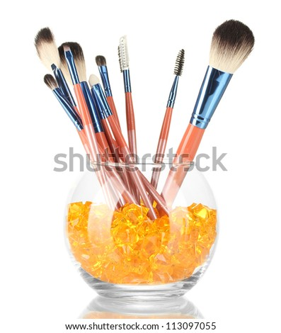 Make-up brushes in a bowl with stones isolated on white