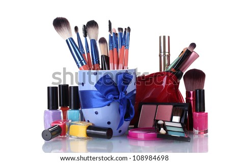 make-up brushes in cup and cosmetics isolated on white
