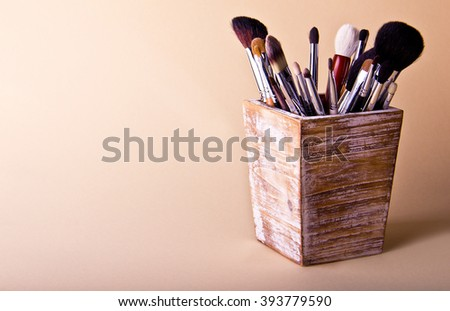 Make up brushes in wooden box on beige background. Place for text.