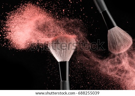 Make-up brushes with pink powder explosion on black background