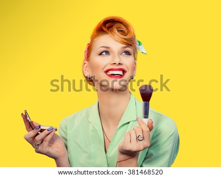 Make up. Close up portrait  headshot of Pinup retro style young woman pretty smiling girl teenager applying foundation powder, blusher with brush in green shirt holding mirror looking at you, camera