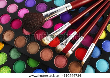 Make-up colorful eyeshadow palette with makeup brushes on it