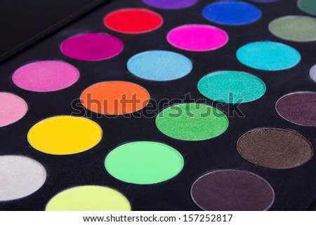 Make up colorful eyeshadow palettes over black background