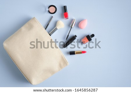Make-up cosmetic bag on blue background. Stylish makeup artist pouch with beauty products. Flat lay, top view Сток-фото ©