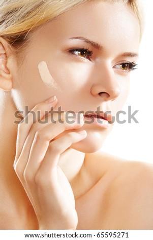 Make-up & cosmetic. Woman applying skin foundation on white backgroun.