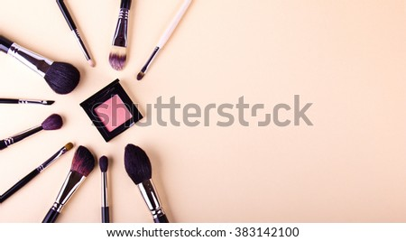 Make up essentials. Set of professional make up brushes and shadows on light beige background. Place for your text or logo. Ideal for beauty blog. Like a star.