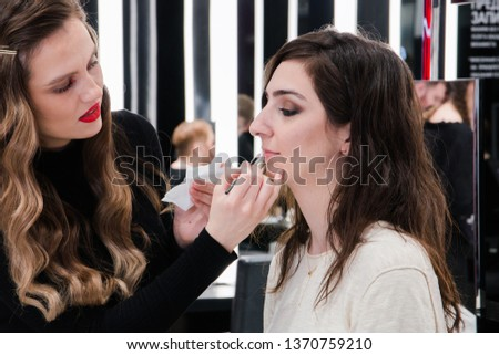 make up girl doing makeup. Open workshop master class makeup art shows on the model technique of applying lipstick from Mac cosmetics, perfect matte lips, Russia, Moscow, April 2019.