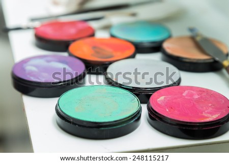 Make up palette with different colors. Brush makeup lying on pallets with different colours.