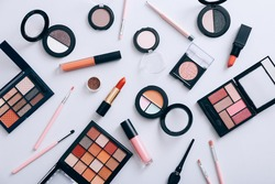 Make up products scattered on gray background, top view
