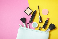 Make up products spilling out of a pastel blue cosmetics bag, on to a bright yellow and pink background with blank space at side