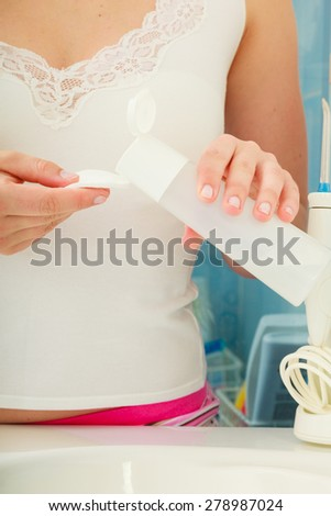 Make up remove skin care. Closeup woman holding cotton swab and makeup remover in hands. #278987024