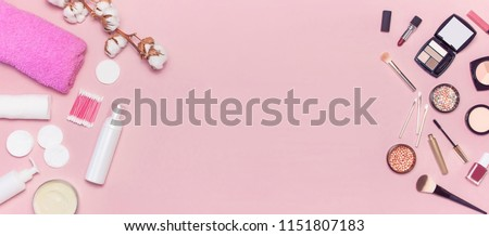 Make-up Remover Accessories. Flat lay background with cotton branch, cotton pads, ear sticks, cosmetic bottle containers, pink towel, various make-up cosmetics, mascara, powder, lipstick, eyeshadow.