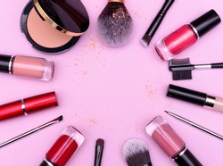 Make up the essentials. A set of professional makeup brushes and cosmetics on a pink background. Space for your text or logo. Perfect for a beauty blog. Flatly, horizontal.