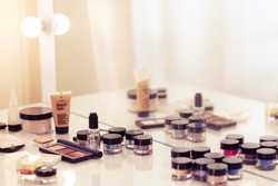 Make up tools on the white table. Eyeshadow, blush, concealer, powder.