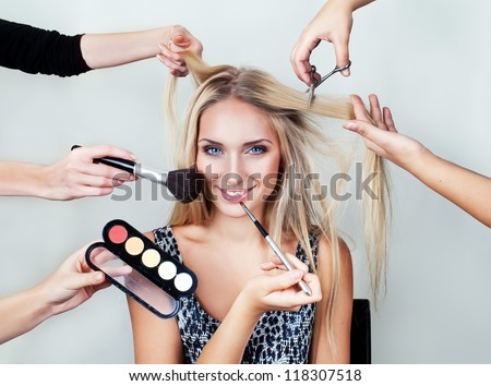 make up woman with many hands. makeup brushes, scissors, shadows.