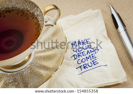 make your dreams come true - motivational slogan on a napkin with cup of tea