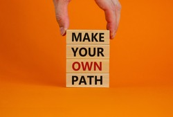 Make your own path symbol. Wooden blocks with words 'Make your own path'. Male hand. Beautiful orange background. Business and make your own path concept. Copy space.