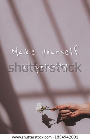 Make yourself a priorty quote on a hand holding flower background Foto stock ©