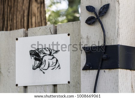 Makeshift beware of dog sign on a decorative fence.