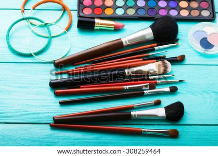 Makeup accessories on blue wooden workspace. Top view