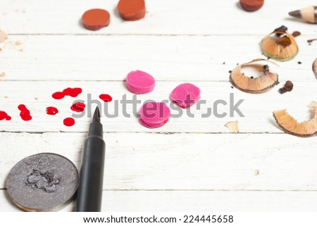 makeup accessories on white wood table