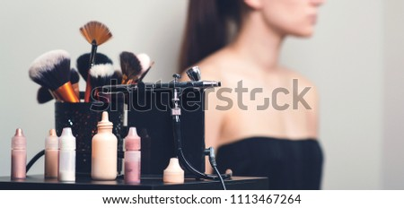Makeup airbrush and the bottles with paint for body art.