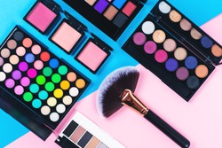 Makeup and beauty products on pink and blue background. Eye shadow palettes. fan contouring brush and blushes. Flatlay, top view.