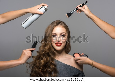 Shutterstock Makeup and hairstyle process, portrait of beautiful young woman and many hands with a brush, powder, comb and hairspray. Studio shot, gray background