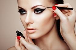 Makeup artist applies eye shadow. Beautiful woman face. Perfect makeup