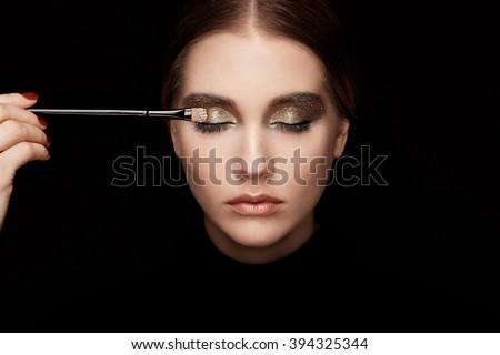 makeup artist applies eye...
