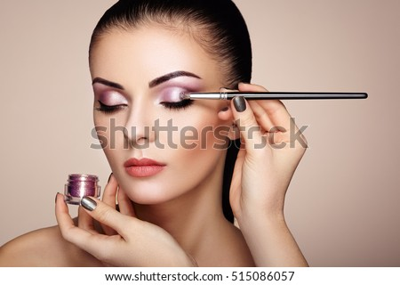 Makeup artist applies eye shadow. Beautiful woman face. Perfect makeup. Makeup detail. Beauty girl with perfect skin. Nails and manicure
