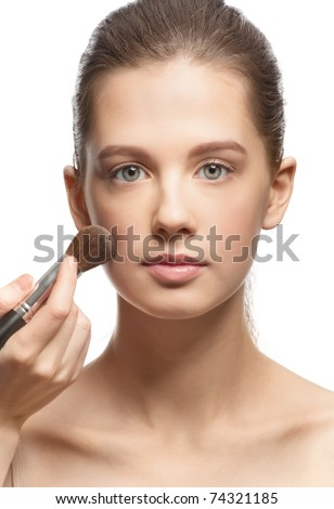 Makeup artist applying makeup on attractive young woman's face, isolated on white