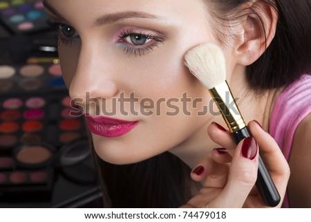 Makeup artist applying shimmer powder on woman face