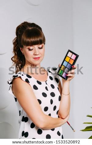 Makeup artist in work. Colorful shadows in hand of makeup artist. Makeup salon. Makeup concept.