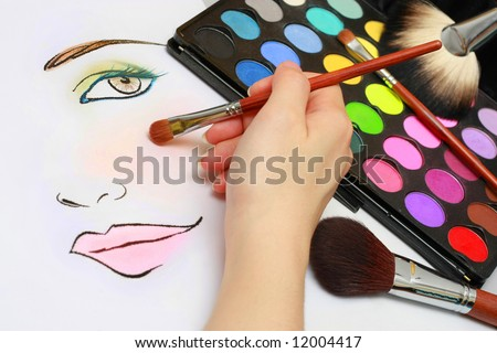 Makeup artist is sketching makeup style on a paper. - stock photo