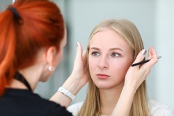 Makeup artist looks at symmetry models eyebrows. During healing process, loss color is minimal. Girl with master agree on shape, technique and shade eyebrows. Contour is filled with color
