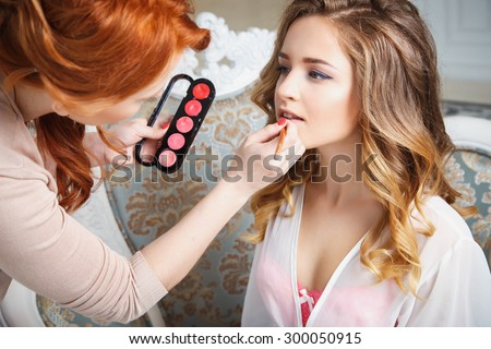 makeup artist preparing bride before the wedding in a morning #300050915