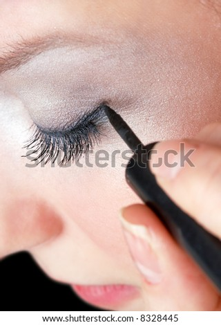 makeup artist tracing eye line with black eyeliner, beautiful girl